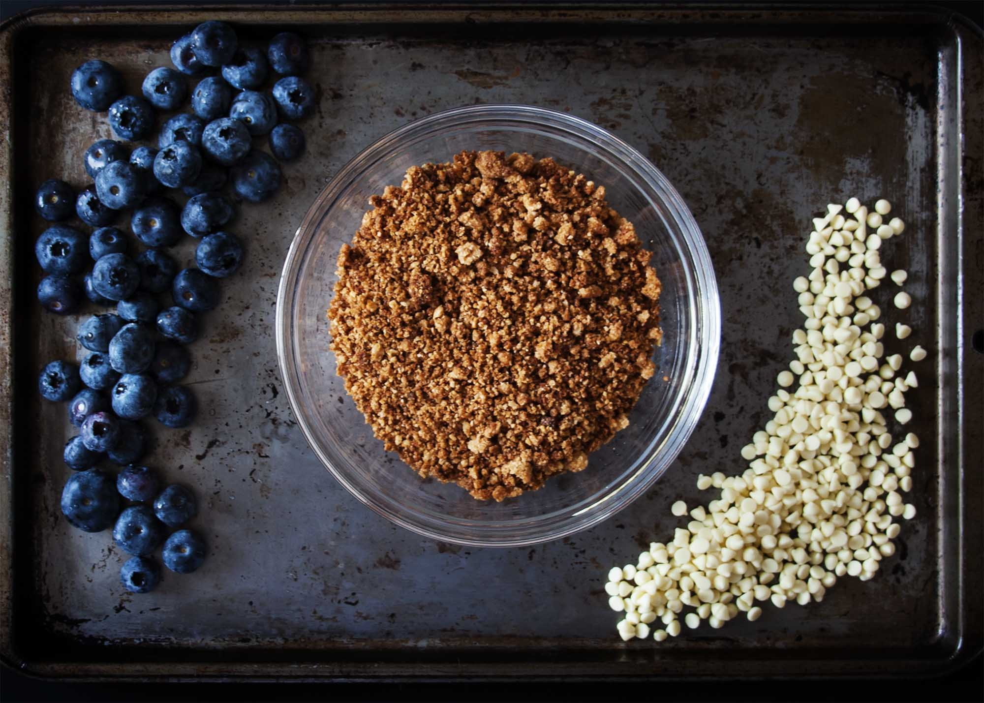 Blueberries, granola, and white chocolate arranged on a baking sheet.