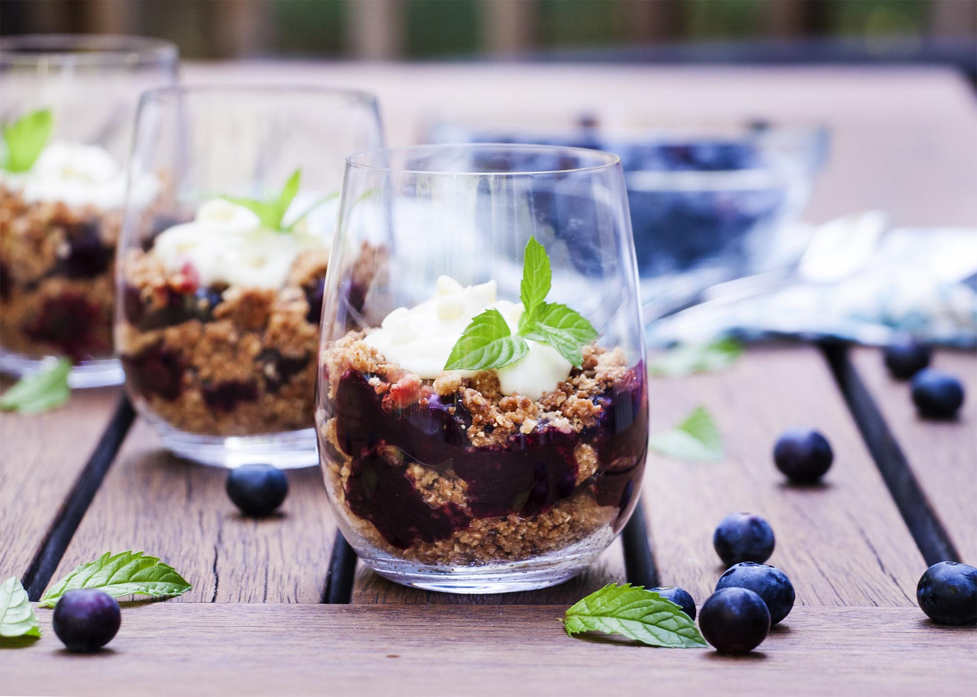 A group of blueberry parfait cups set out on a table with blueberries and mint leaves scattered about.