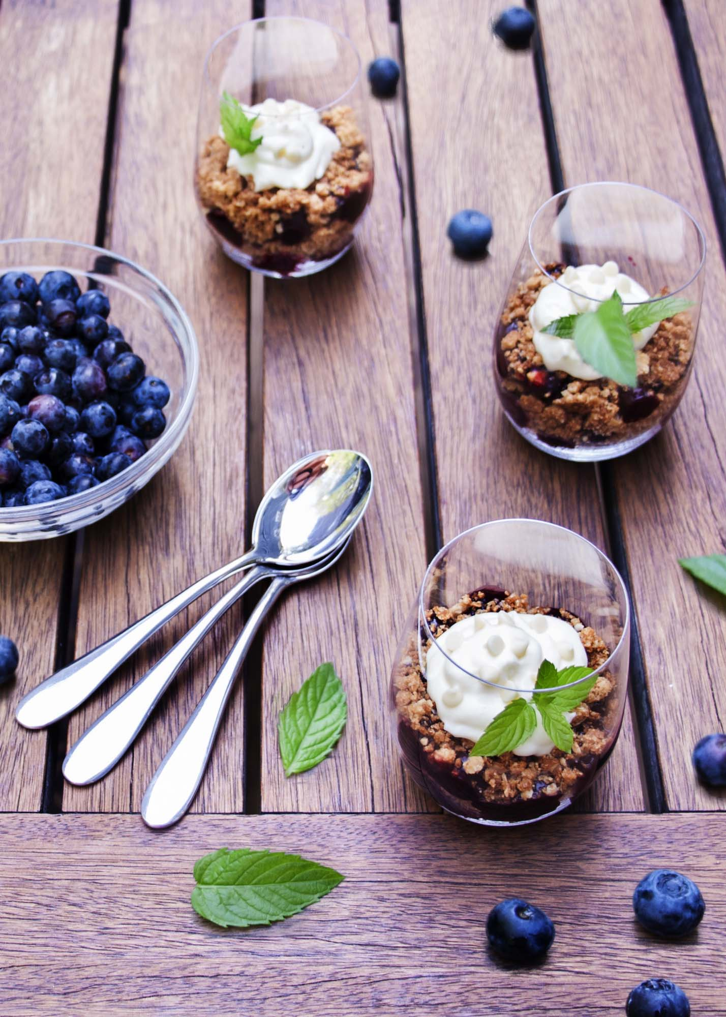 A table set with blueberry pie parfaits and spoons.