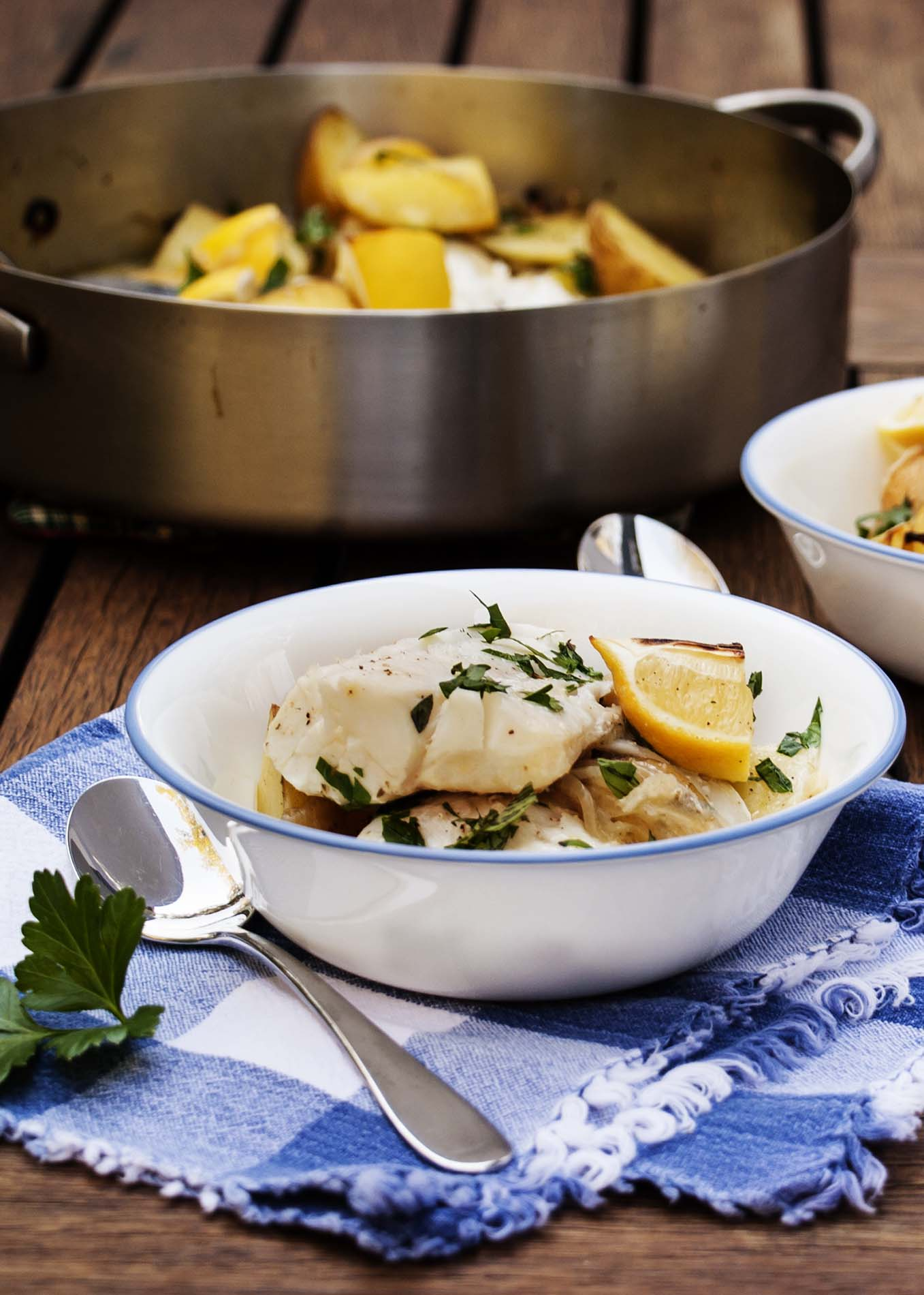 Cod Baked With Lemon and Potatoes - Simple and delicious. This oven to table dish features thick cod fillets combined with creamy potatoes and onions, all baked in a sauce of lemons and olive oil | justalittlebitofbacon.com