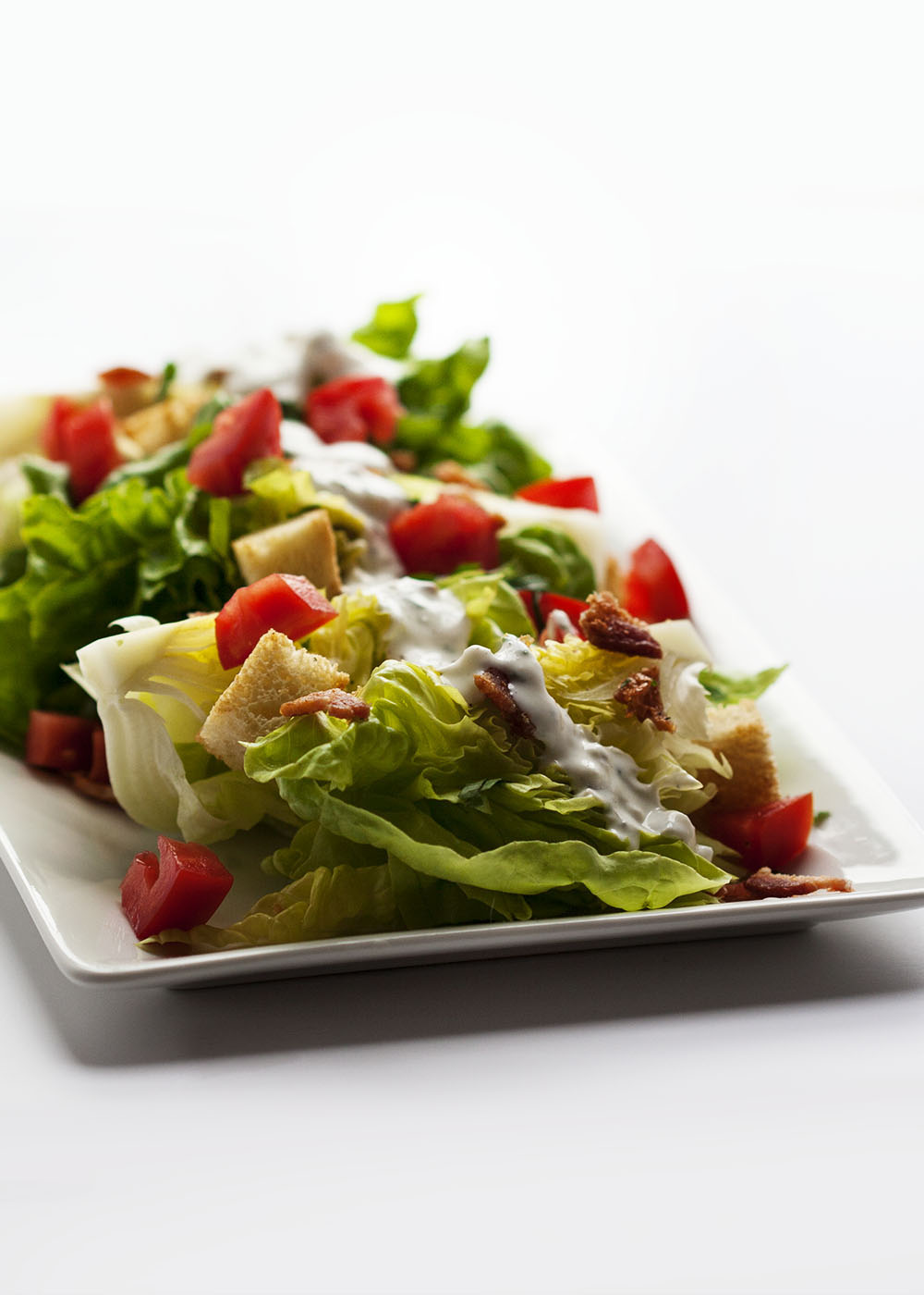 Blue Cheese and Bacon Wedge Salad - Creamy blue cheese, crispy bacon, and ripe tomatoes combine with tender lettuce in this version of the classic salad.   justalittlebitofbacon.com