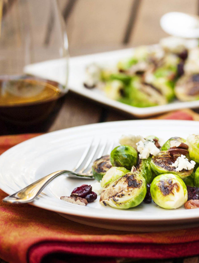 Blue Cheese and Brussels Sprout Salad - Pan roasted Brussels sprouts are paired with blue cheese and tossed with a tangy mustard vinaigrette in this fast and flavorful salad. | justalittlebitofbacon.com