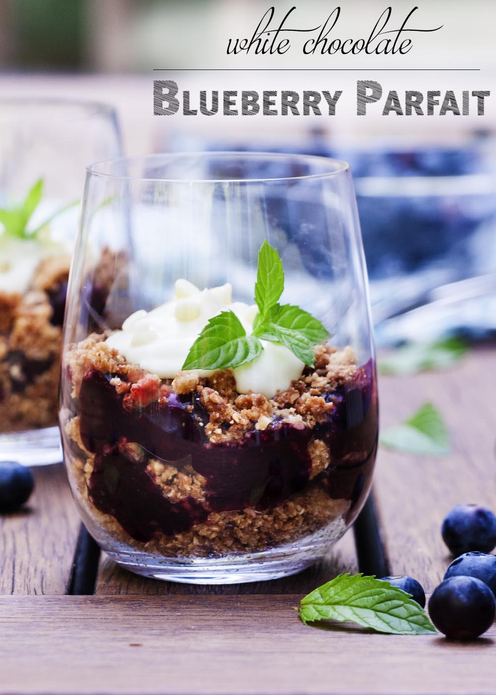 For a great summer dessert, perfect for parties, try this recipe for blueberry parfaits topped with white chocolate cream! Layers of blueberry pie filling and crunchy granola make for a tasty treat. | justalittlebitofbacon.com