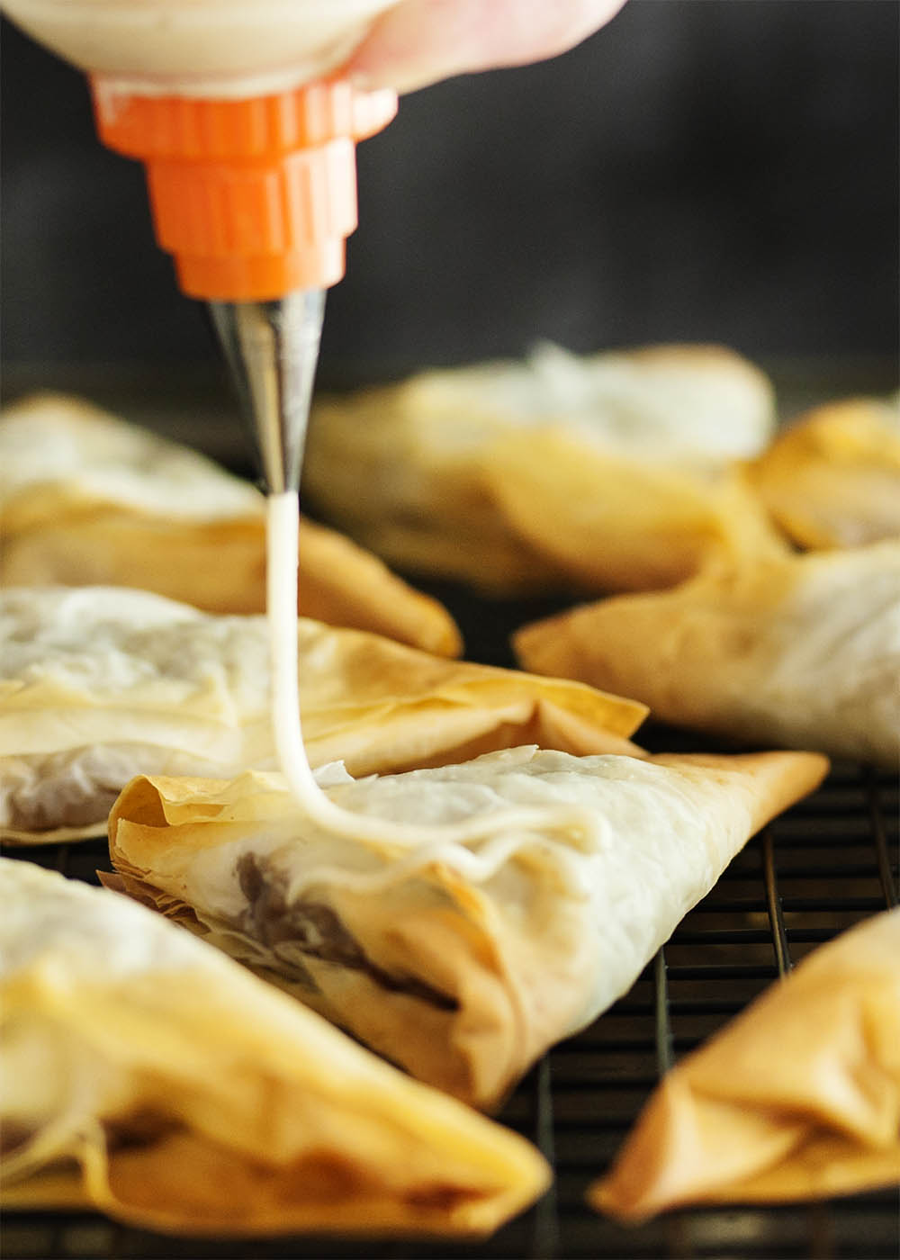 Spiced Honey Apple Turnovers - Layers of flaky fillo dough are wrapped around a filling of apples and honey all flavored with warm spices. Add a drizzle of honey icing on top and you have an apple turnover that will have you wanting more. | justalittlebitofbacon.com