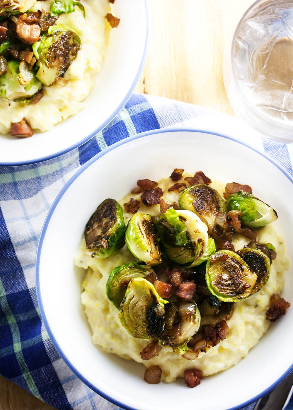 Creamy Polenta Topped with Brussels Sprouts and Pancetta - Pan roasted brussel sprouts, crispy pancetta, and creamy, cheesy polenta all in one bowl? That's the definition of yummy. | justalittlebitofbacon.com