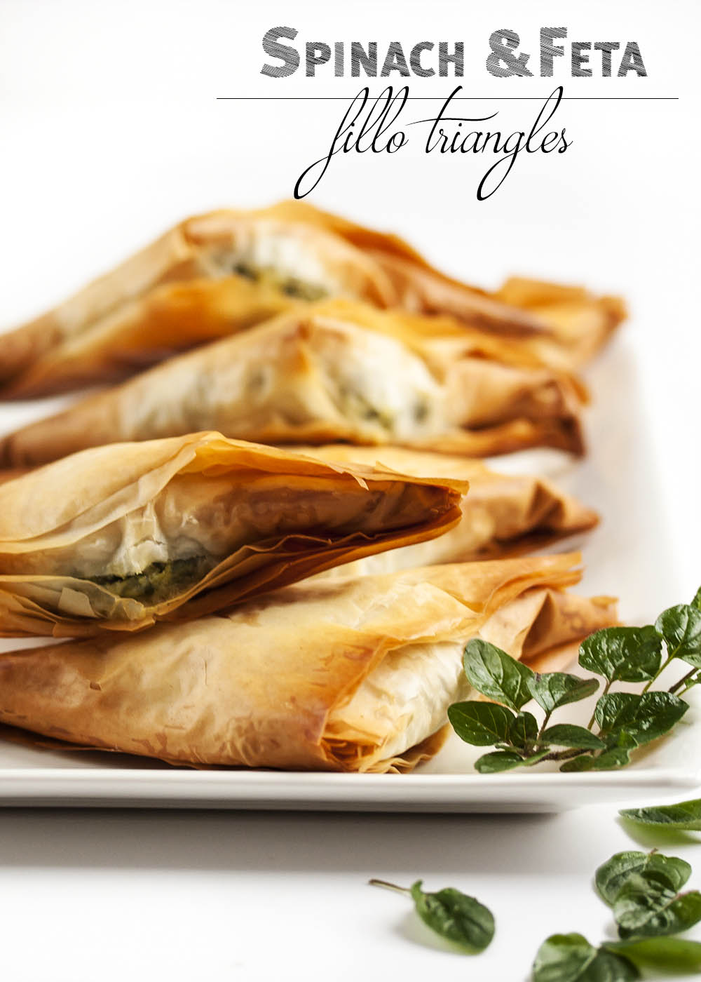 Spinach Feta Fillo Triangles - A great addition to a party or a fun side dish for a special meal, these Spinach Feta Triangles will be a hit with their classic combination of tasty spinach and salty, creamy cheese. | justalittlebitofbacon.com