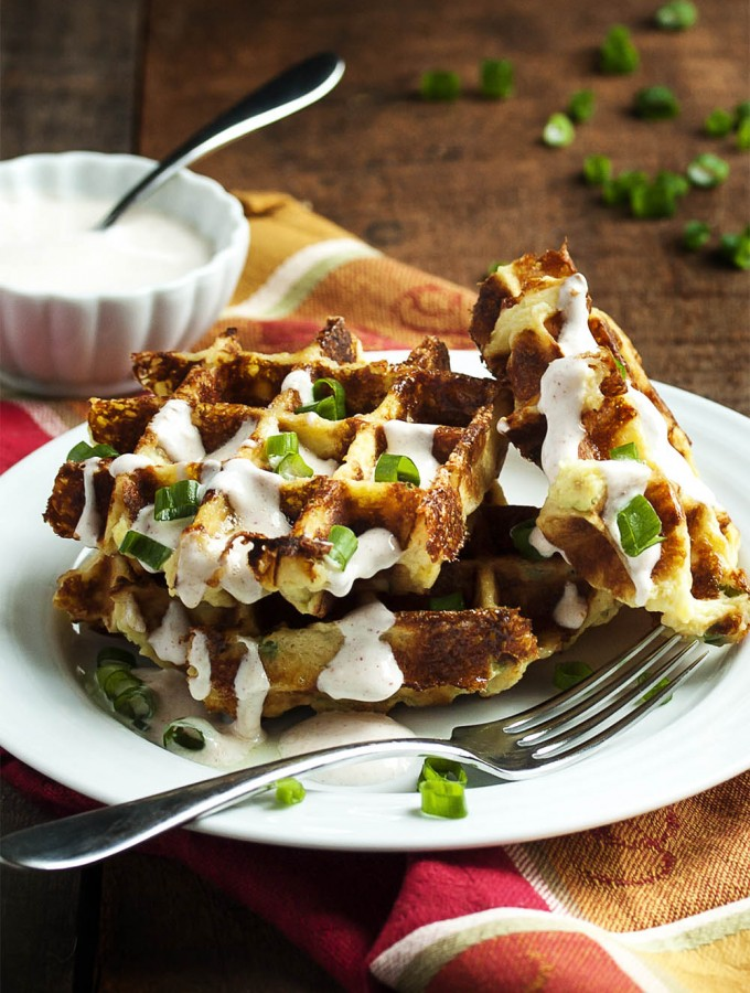 Loaded Mashed Potato Waffles - Mashed Potato Waffles are filled with scallions and cheese and are an awesomely tasty way to enjoy leftover mashed potatoes. Once you try them you may find yourself making mashed potatoes specifically to enjoy these waffles! | justalittlebitofbacon.com