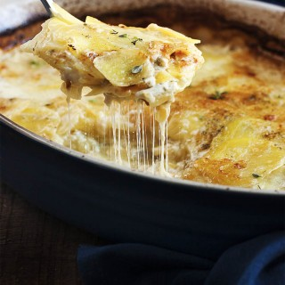 Classic Potato Gratin with Gruyere Cheese - In this classic and simple version of potato gratin, thinly sliced yellow potatoes alternate with layers of shredded gruyere, which is all bound together with garlic infused milk and baked to perfection. | justalittlebitofbacon.com