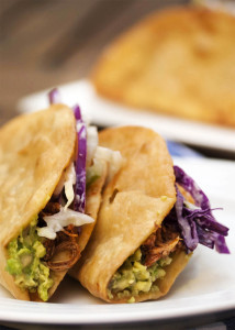 Beer Braised Pulled Chicken Tacos - These pulled chicken tacos feature slow cooked chicken braised in beer and finished with adobo sauce all layered with spicy coleslaw and guacamole. | justalittlebitofbacon.com