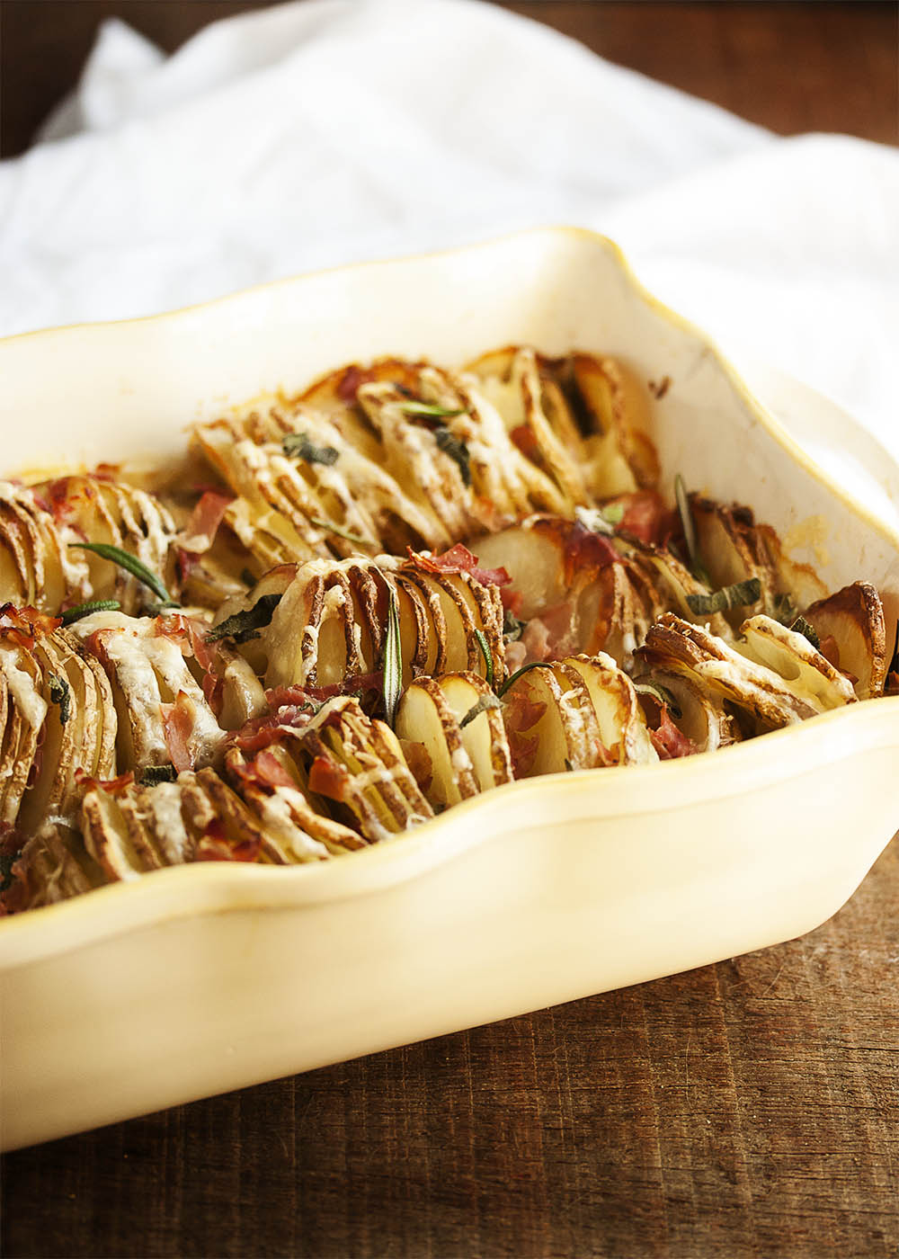 A casserole dish filled with browned and crispy spiralized hasselback potato gratin.