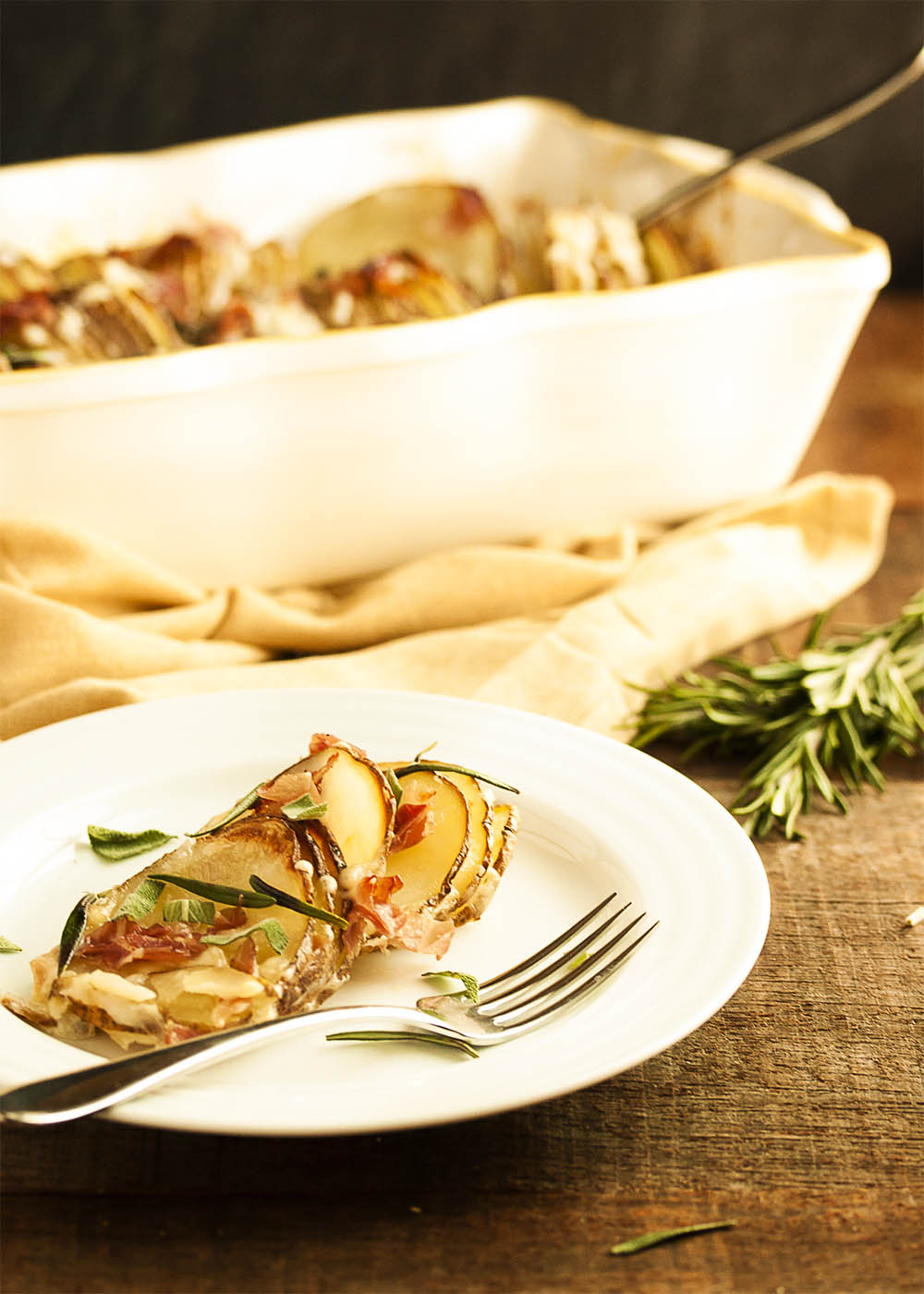 A plate with a serving of hasselback potato gratin with the casserole dish in the background.