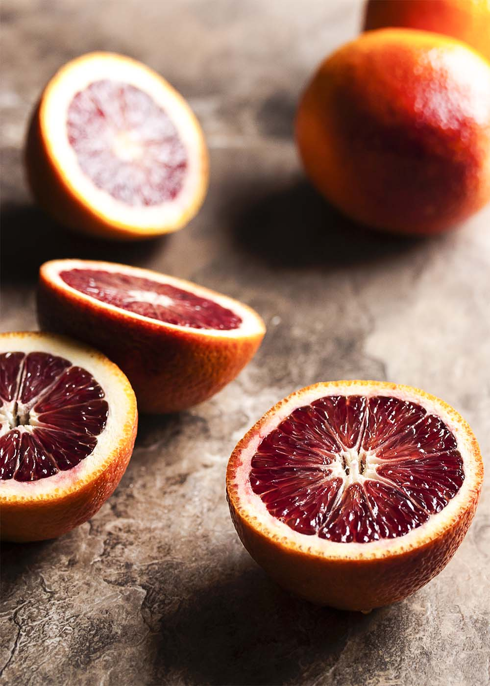 Cut blood oranges on a table showing the deep red color of flesh.