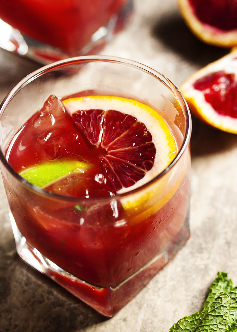 Blood Orange Bourbon Smash - Blood oranges give this Bourbon Smash a gorgeous ruby color. Maple syrup provides a bit of smokey, sweetness while lime and mint give the drink an extra pop of flavor. Have it as is for smooth sipping or add a splash of soda water for a lively cooler.   justalittlebitofbacon.com