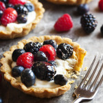 Mascarpone Fruit Tart - This fruit tart is filled a mixture of mascarpone cheese, cream cheese, and heavy cream all of which is whipped up and sweetened with maple syrup. It is then topped with mixed berries and brushed with a simple apricot jelly glaze. | justalittlebitofbacon.com