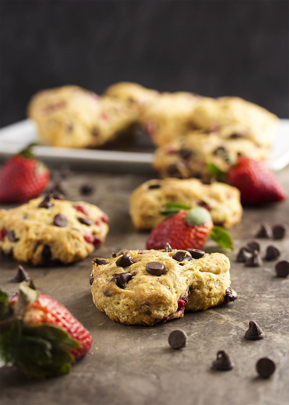 A heart shaped strawberry scone topped with chocolate chips on a table with more scones in the background.