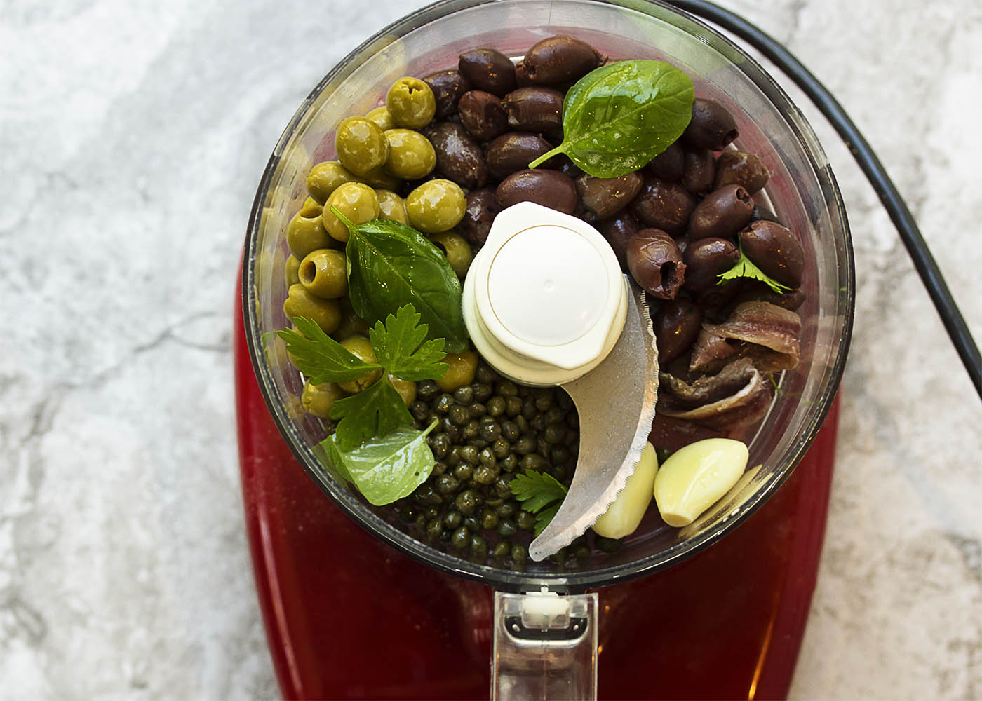 5 Minute Tapenade Mayonnaise - Black and green olives combine with oil-packed anchovy fillets, capers, and a dollop of mayo in this quick, easy, and yummy tapenade. Great as a dip, a topping for bruschetta, alongside grilled meats and fish, or in any other recipe that needs a hit of flavor. | justalittlebitofbacon.com