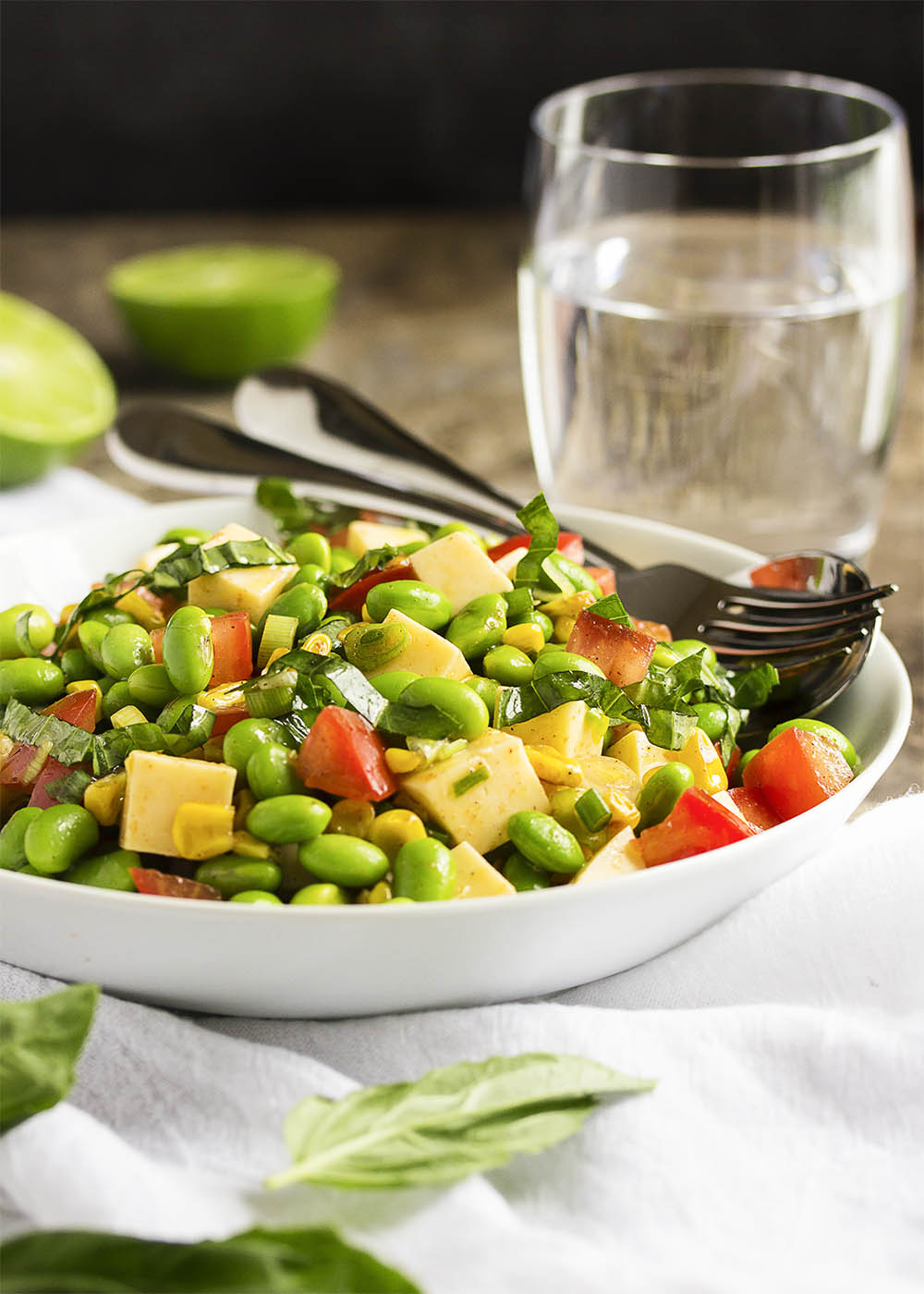 A bowl of edamame, tomato, and corn salad with serving spoon in the bowl.
