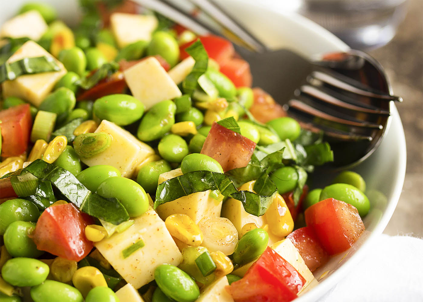 Closeup of the edamame salad showing the corn, tomatoes, basil, cheese, scallions.