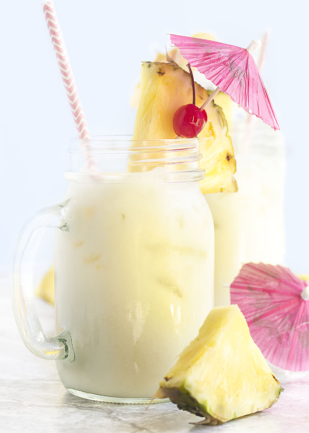 Close up of a perfect pina colada with a straw in the glass. Pineapple slices and drink umbrellas scattered about.