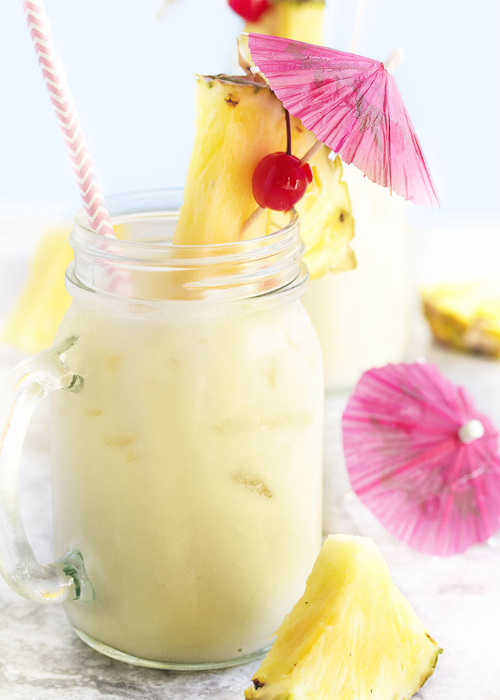 A mason jar glass full of pina colada and ice all garnished with pinapple slices and an umbrella.