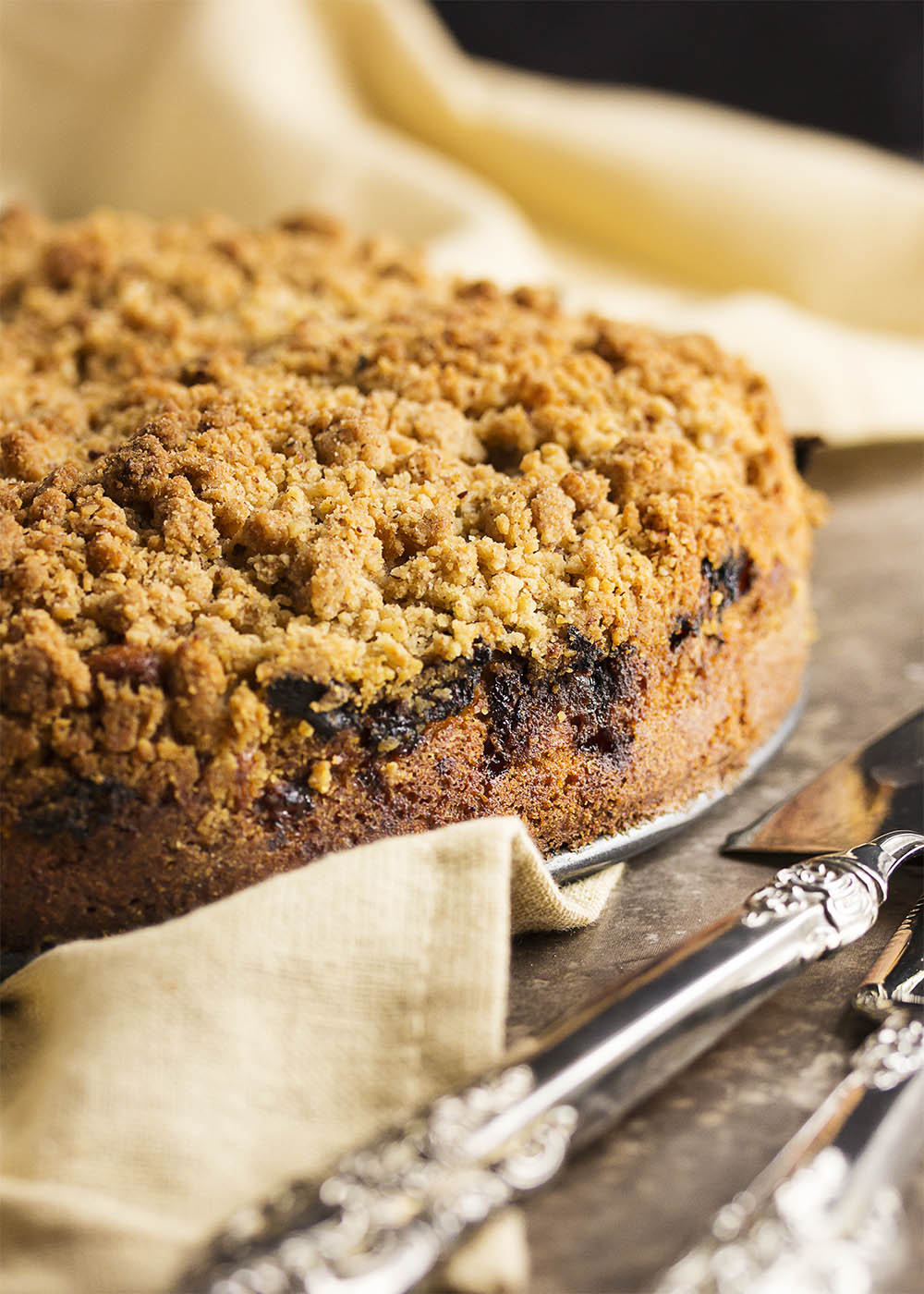 A whole rhubarb coffee cake with crumb topping on a table ready to be served.