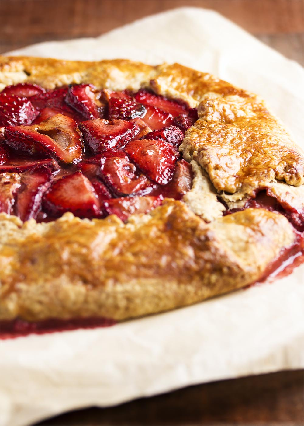 A whole strawberry ricotta crostata full of fresh strawberries and brushed with a honey glaze.