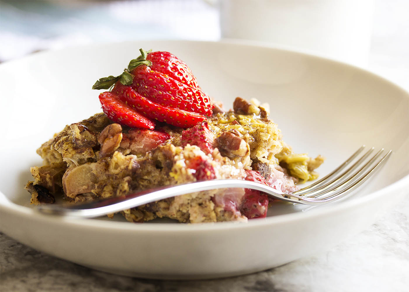 Strawberry Rhubarb Baked Oatmeal - This baked oatmeal smells like a cross between strawberry rhubarb pie and pancakes as it bakes. And it tastes as wonderful as it smells! Pour a little cream over the top, spoon some yogurt next to it, or eat it as is. It's all good. | justalittlebitofbacon.com