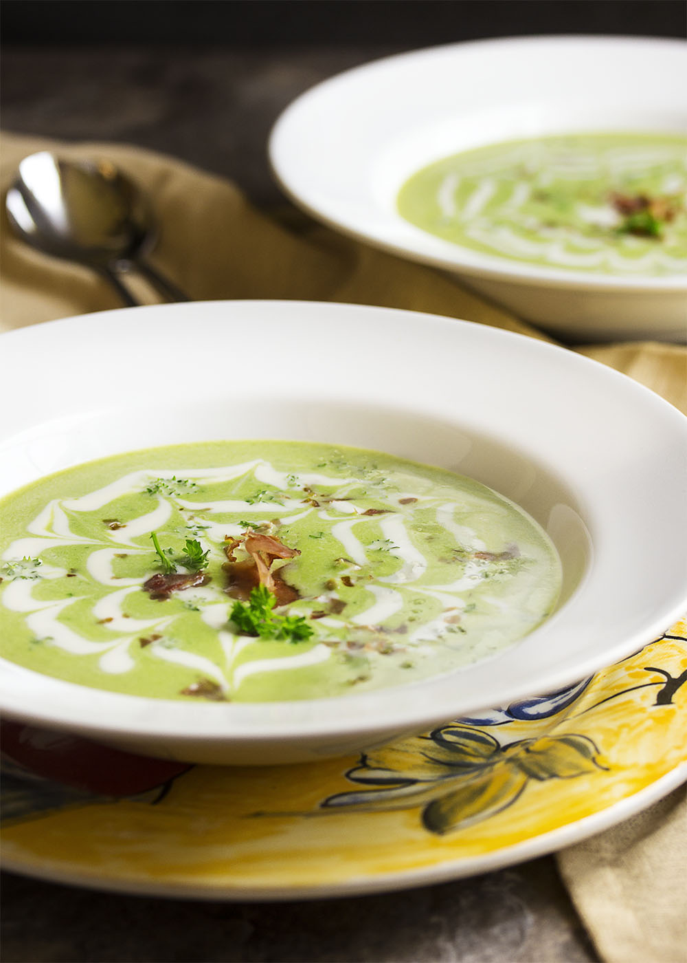 A wide bowl of chilled spring pea soup swirled with creme fraiche and topped with crispy proscuitto.
