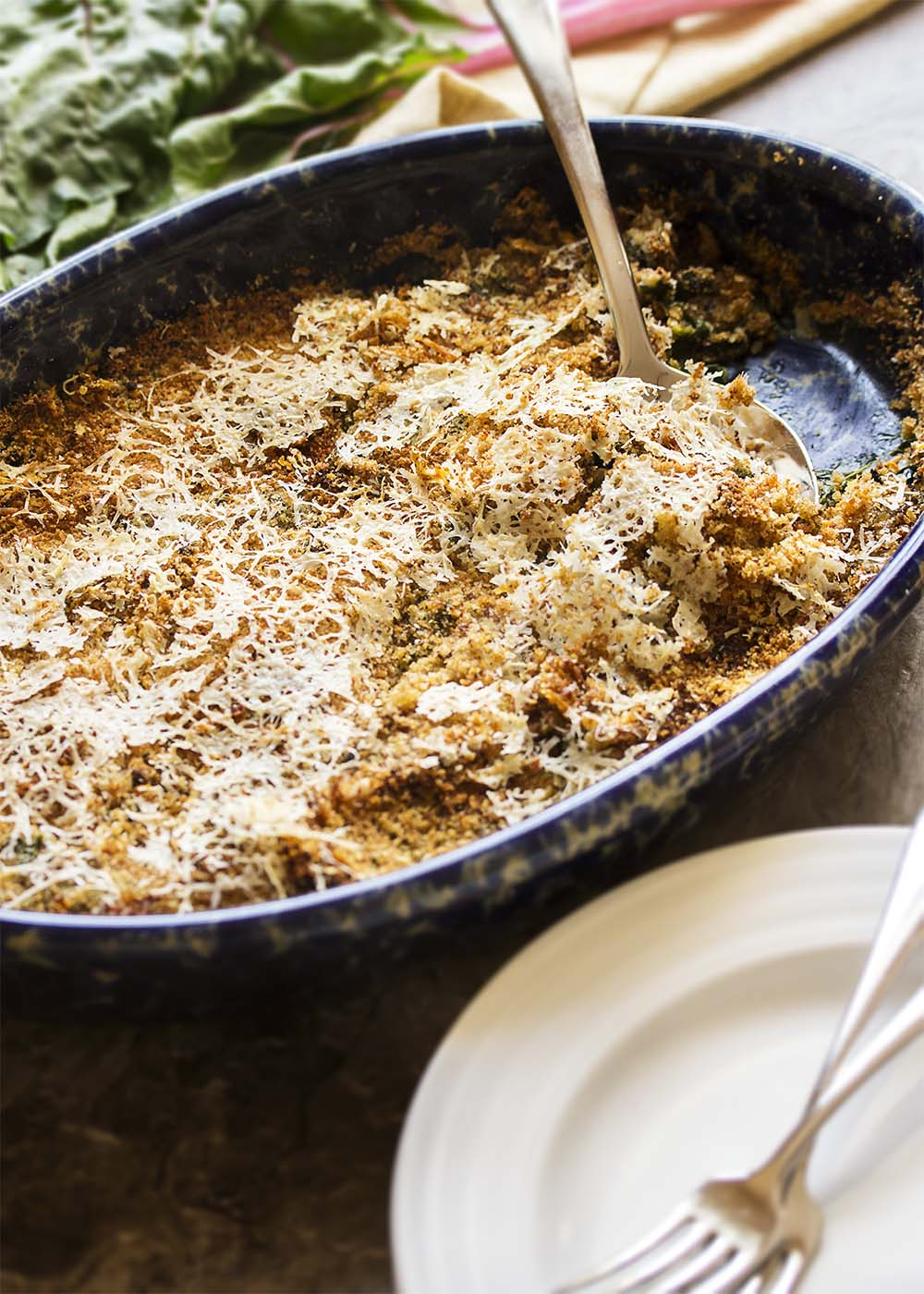 Easy Swiss Chard Gratin - This easy chard gratin is all about the greens as they are cooked in milk and then topped with breadcrumbs and a handful of parmesan. This a great gratin for when you have more greens than you know what to do with - chard, kale, turnip greens, beet greens, spinach. Try a mix of different greens!   justalittlebitofbacon.com