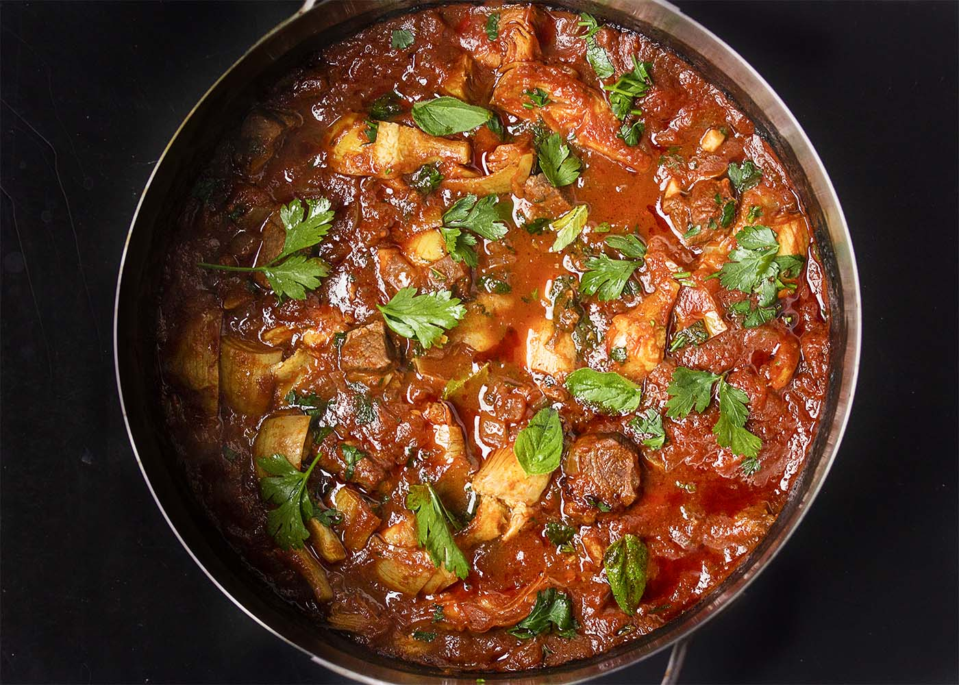 Top view of a big pot of spring Greek lamb stew with artichokes and fresh herbs.