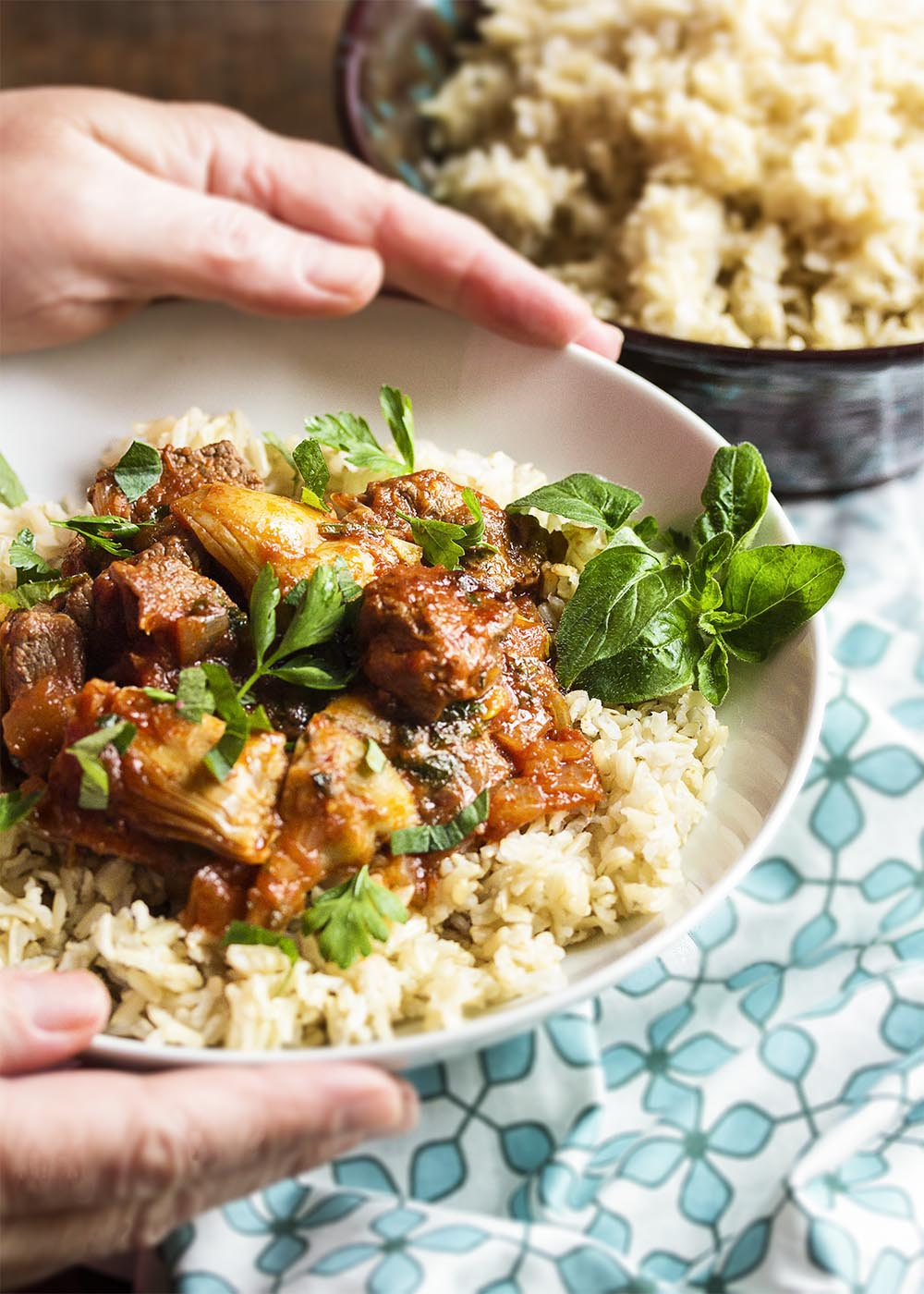 Hands holding up a bowl of brown rice topped with lamb and artichoke stew. Fresh parsley and oregano scattered over the top.