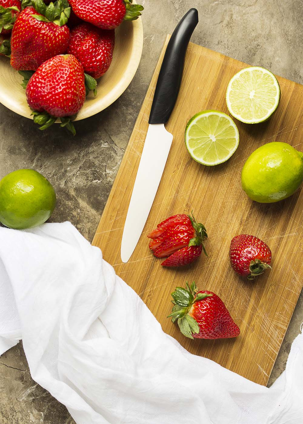 A cutting board with a knive showing how to make the garnishes for the daiquiri.