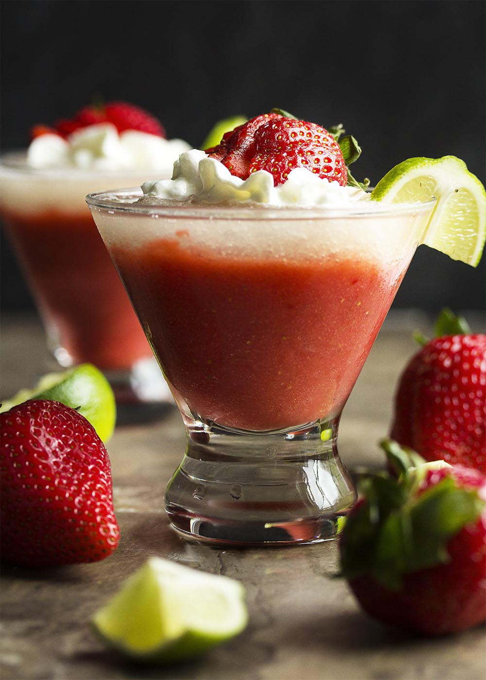 Side view of a frozen strawberry daiquiri with a layer of lime daiquiri on top. The drink garnished with whipped cream, sliced strawberries, and a lime slice.