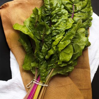 Ingredient Spotlight: Swiss Chard - Swiss chard is a wonderful, hearty green that is great in soups, gratins, pastas, and many other recipes. Its flavor is a cross between spinach and beets and you'll love cooking with it once you give it a try. | justalittlebitofbacon.com