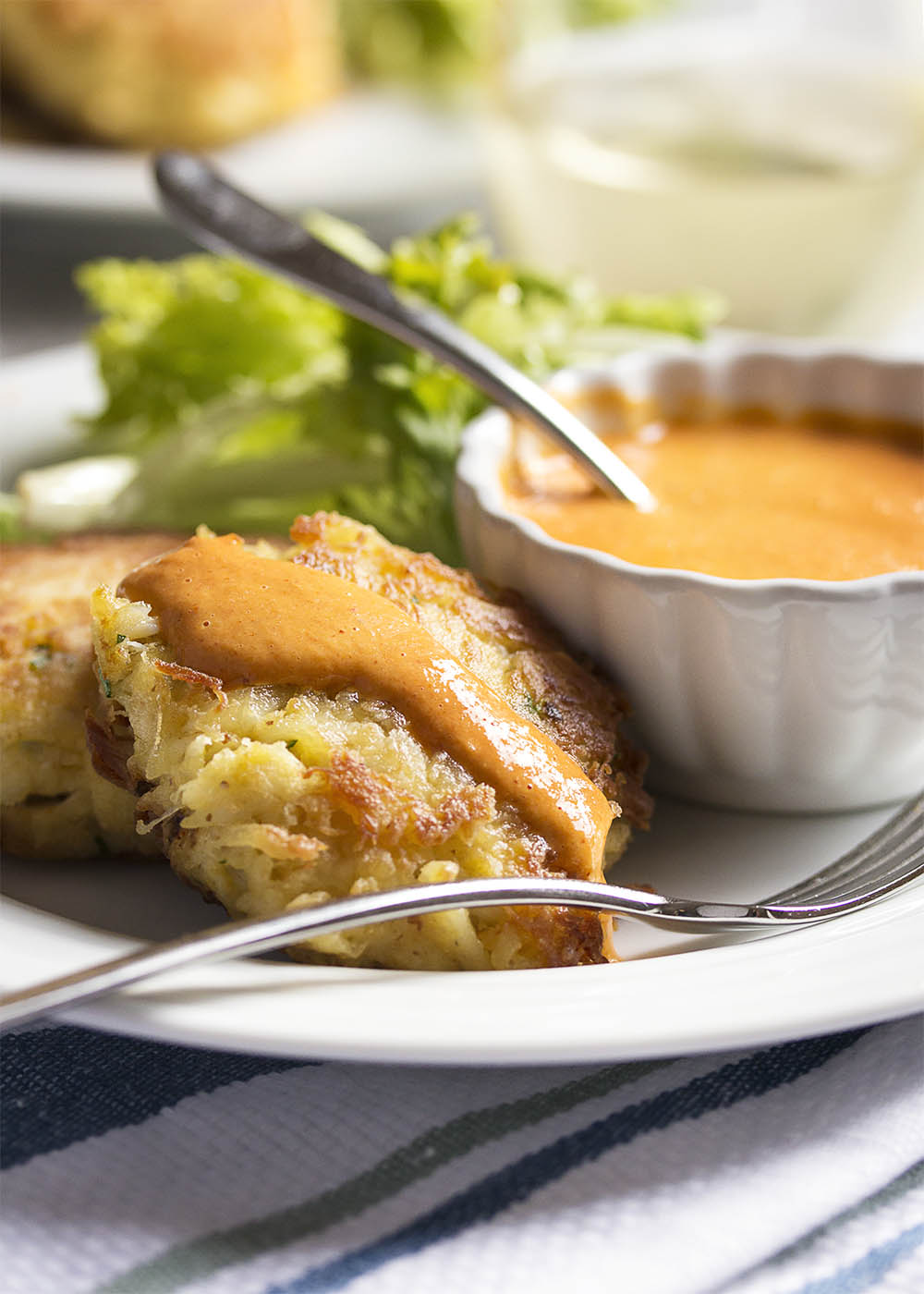 Crab Cakes with Creamy Roasted Red Pepper Sauce - Crab cakes take on Spanish flavors with these paprika spiced cakes which are served alongside a tangy roasted red pepper and cream sauce.   justalittlebitofbacon.com