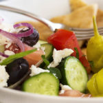 Greek Chopped Salad - Greek chopped salad is a great, healthy Mediterranean recipe full of tomatoes, cucumbers, onion, olives, and feta cheese. I also add in some fresh herbs and toss it all with a lemony dressing. | justalittlebitofbacon.com