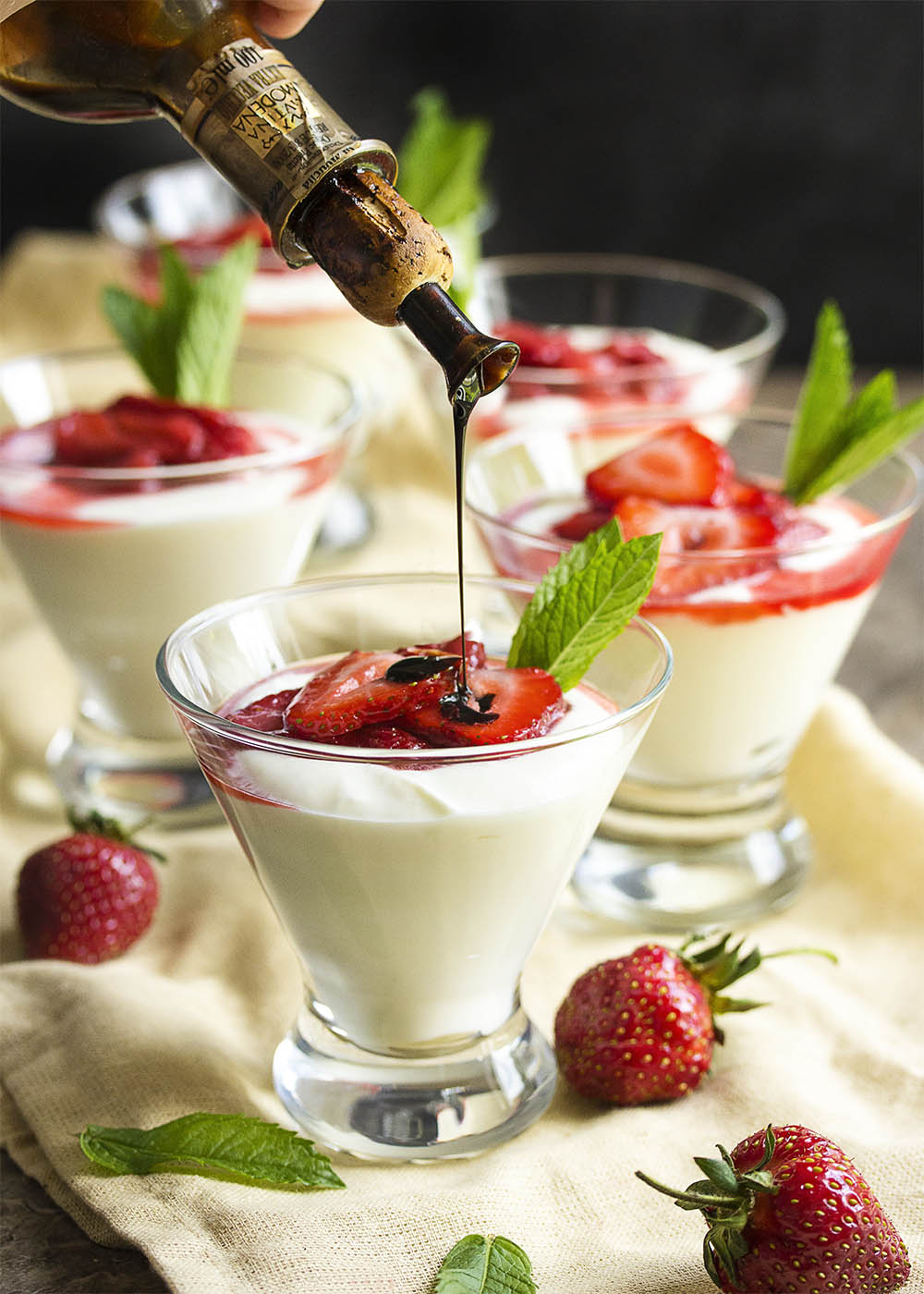 Martini glasses filled with mascarpone mousse and topped with fresh strawberry sauce and drizzled with balsamic vinegar.