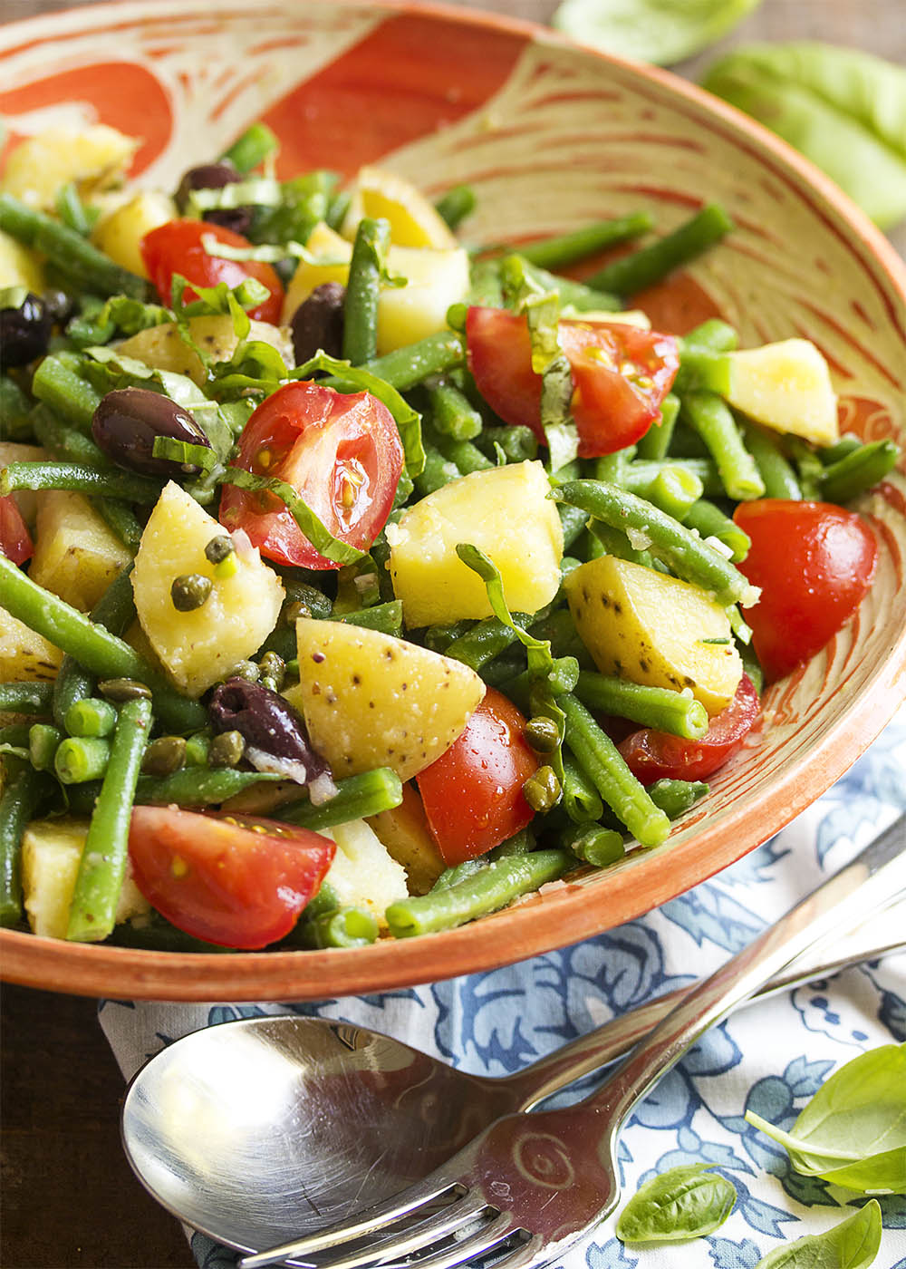 Potato Salad Nicoise - This tasty and relaxed version of salad nicoise mixes green beans, potatoes, olives, and tomatoes with a lemony, anchovy spiked dressing. Add all the ingredients to the salad bowl, toss with the dressing, and dinner is served!   justalittlebitofbacon.com