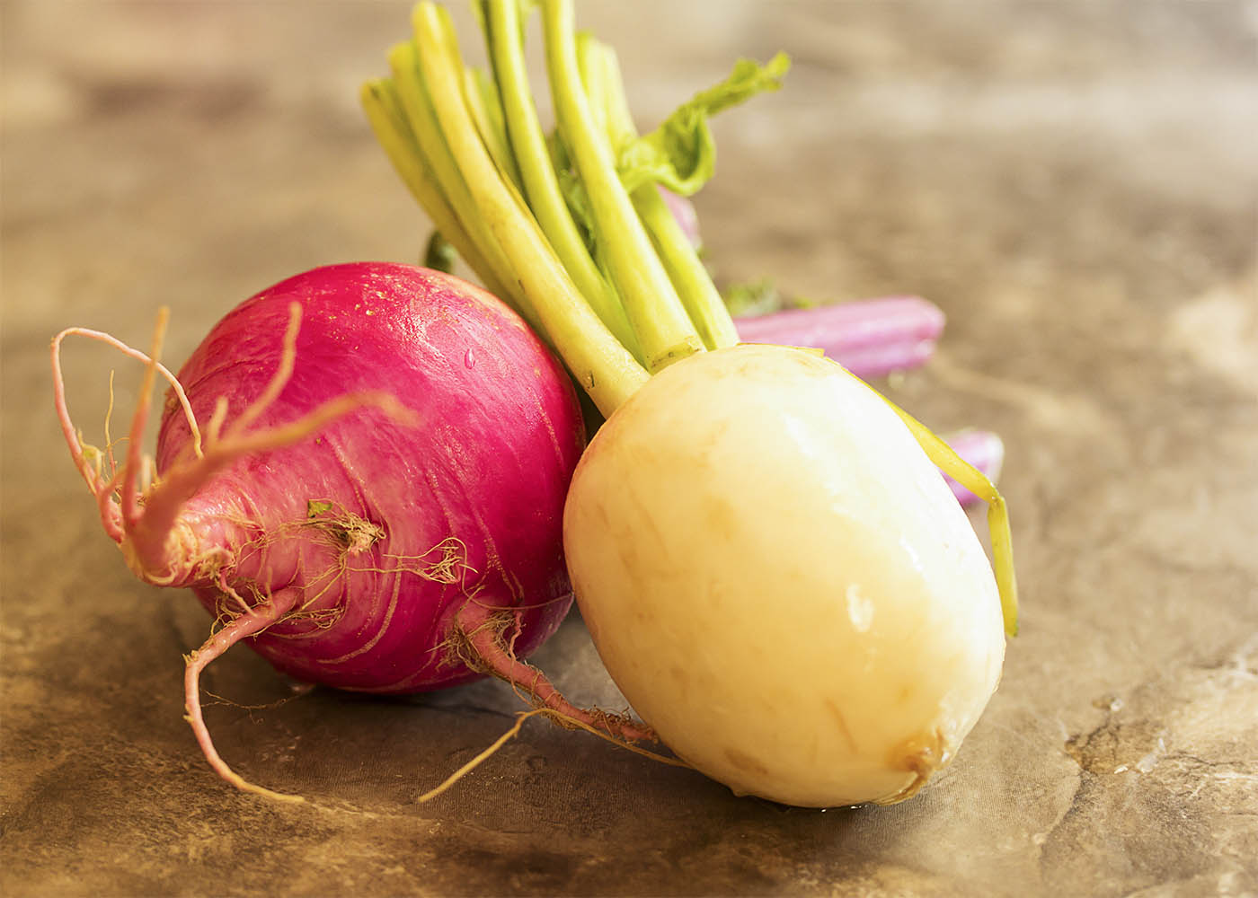 Two turnips on a table - one white turnip and one red turnip.