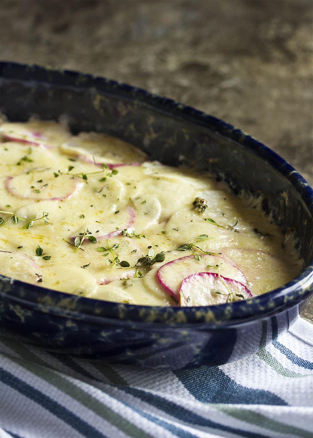 A casserole dish of simple turnip gratin topped with melted gruyere cheese and fresh thyme.