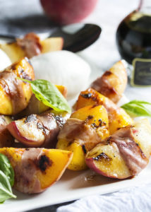 Balsamic Grilled Peaches with Burrata and Prosciutto - Sweet, salty, creamy, and tart combine in this recipe to create a recipe full of bold flavors. Juicy, sweet peaches are wrapped in prosciutto and seared on the grill, then drizzled with balsamic vinegar and paired with burrata. Wonderful as an appetizer or as a side dish. | justalittlebitofbacon.com