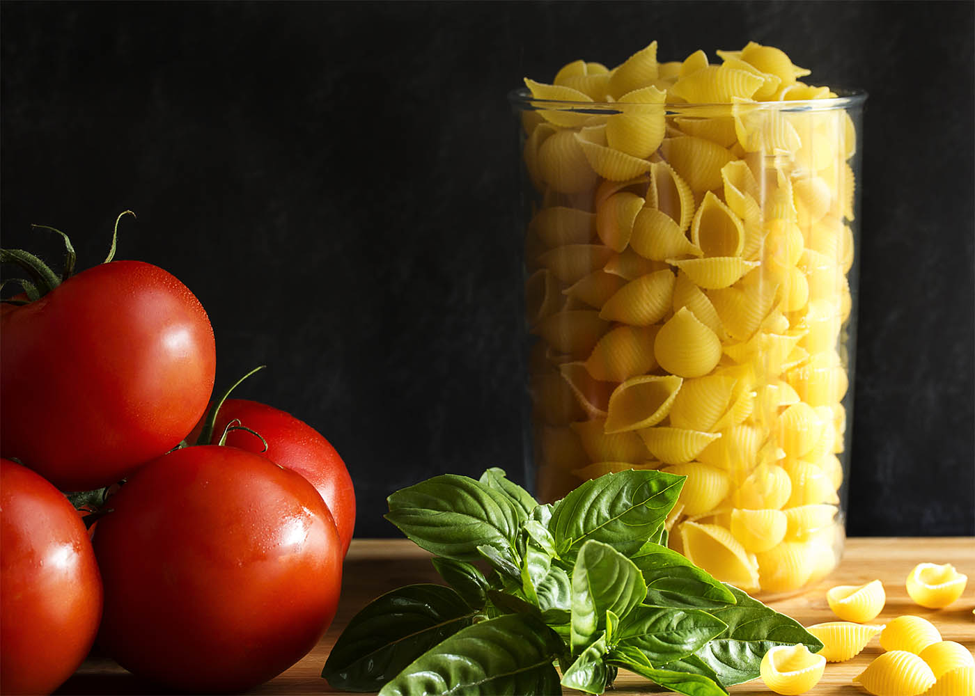 The main ingredients in pasta with raw tomato sauce - pasta shells, ripe tomatoes, and fresh basil leaves.