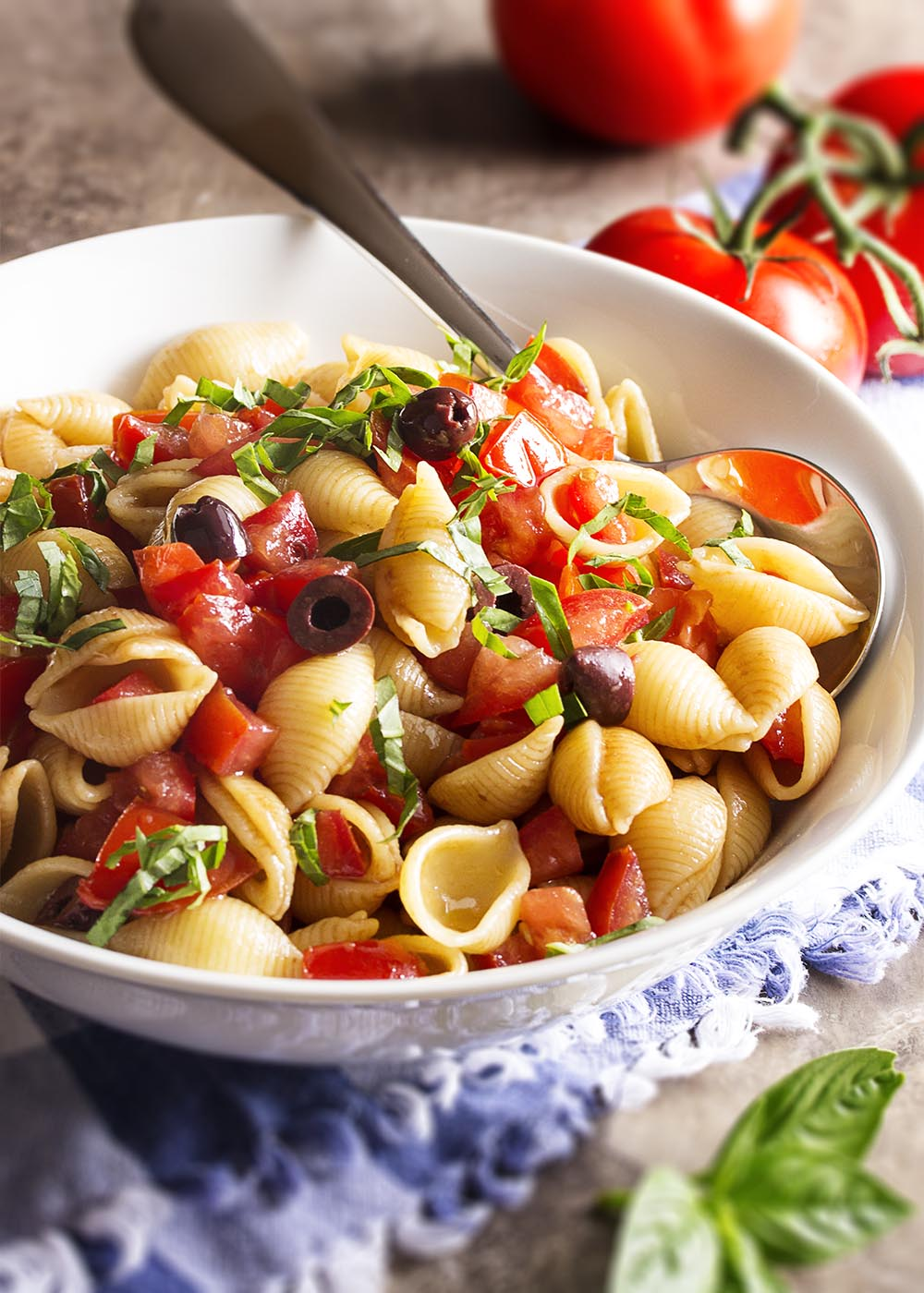 A large serving bowl of freshly cooked pasta shells tossed with ripe tomatoes, olives, basil, and olive oil.