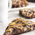 Triple Chocolate Banana Scones - These triple chocolate scones are studded with banana chunks in an intensely chocolatey batter and then topped with chocolate glaze and a peanut butter drizzle. Have them for breakfast or dessert and they would be perfect for a brunch. | justalittlebitofbacon.com