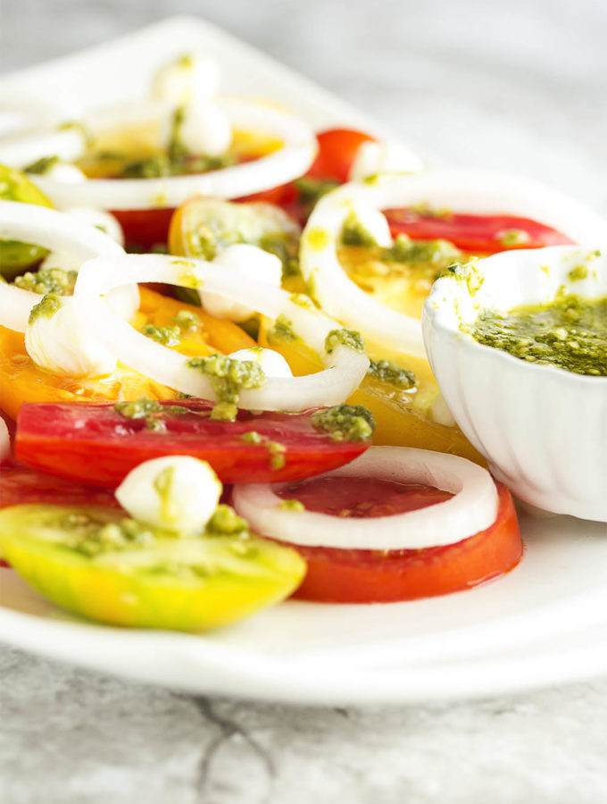 Heirloom tomatoes are sliced up with sweet onions and mozzarella pearls and then drizzled with balsamic pesto in this caprese salad. | justalittlebitofbacon.com
