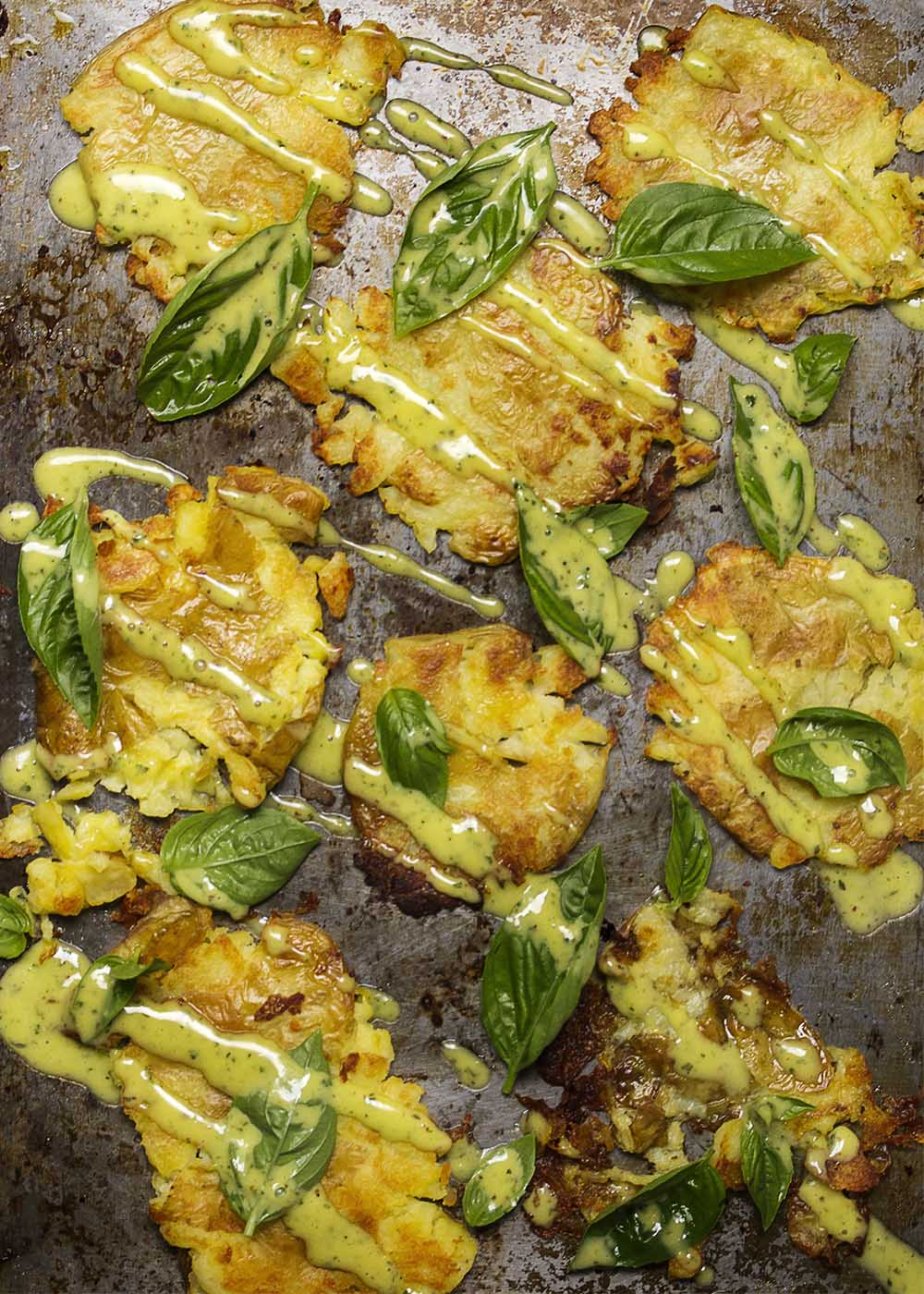Crispy Roasted Smashed Potatoes - These crispy and easy roasted smashed potatoes make a great side dish. Cook the potatoes ahead and then smash them flat and crisp them in the oven. Serve them with a basil aioli to put them over the top.   justalittlebitofbacon.com