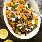 Cold sweet potato salad is topped with dried cranberries and pecans, then tossed with a maple syrup and mustard dressing. Perfect for summertime picnics and for the Thanksgiving table. | justalittlebitofbacon.com