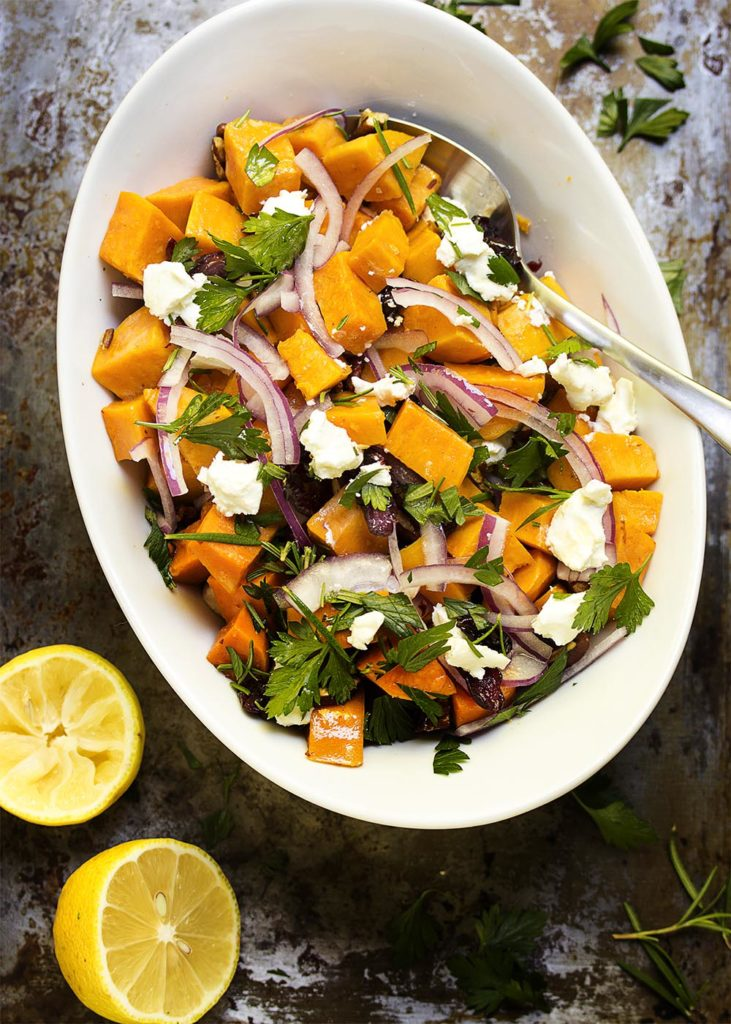 Cold sweet potato salad is topped with dried cranberries and pecans, then tossed with a maple syrup and mustard dressing. Perfect for summertime picnics and for the Thanksgiving table.   justalittlebitofbacon.com