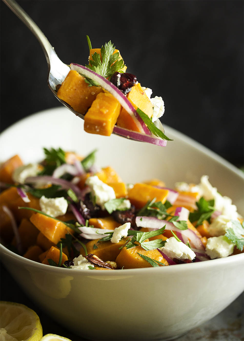 A big spoonful of sweet potato salad showing the sweet potatoes, onions, cranberries, pecans, goat cheese, and herbs.