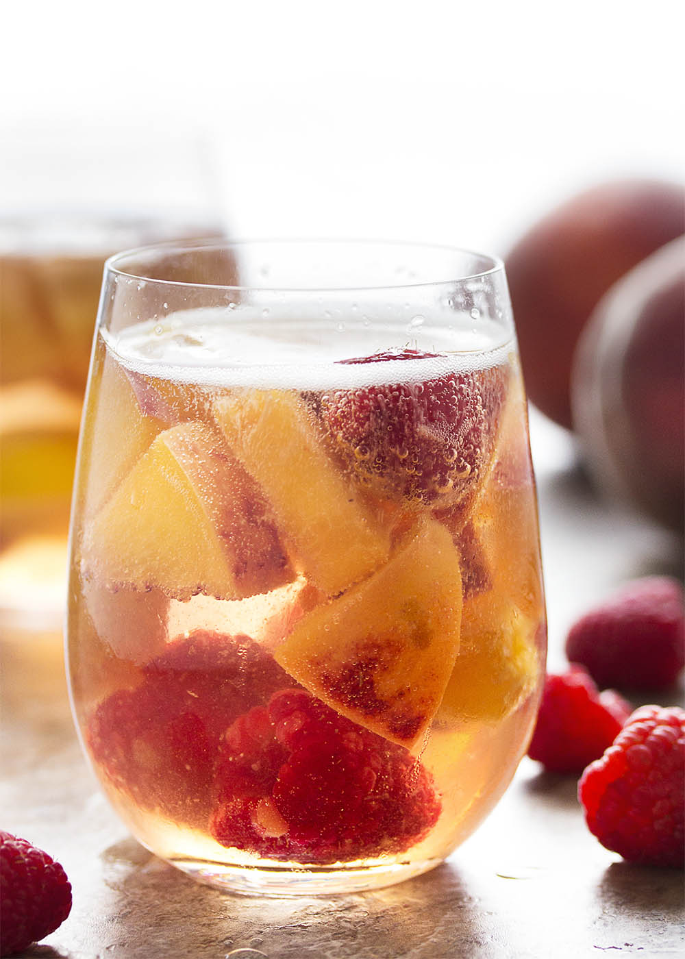 This sparkling white peach sangria is super easy to mix together and just as easy to enjoy on a warm day. Not too sweet and full of fizz from the bubbly, it's the taste of summer in a glass! | justalittlebitofbacon.com
